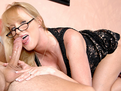 Busty blonde cougar sucks cock while wearing glasses