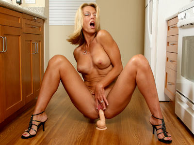 Golden bronze toned cougar Brenda James rides a thick dildo in the kitchen from Anilos.com