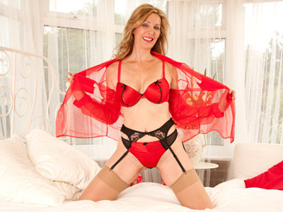 sultry cougar in red lingerie plays with a vibrator