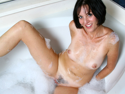 Dark haired milf with tan lines fucks a dildo in theme bath tub