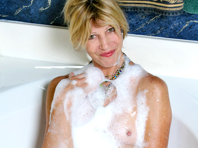 Wild cougar Rosetta gets off from behind the bath water splashing her pussy