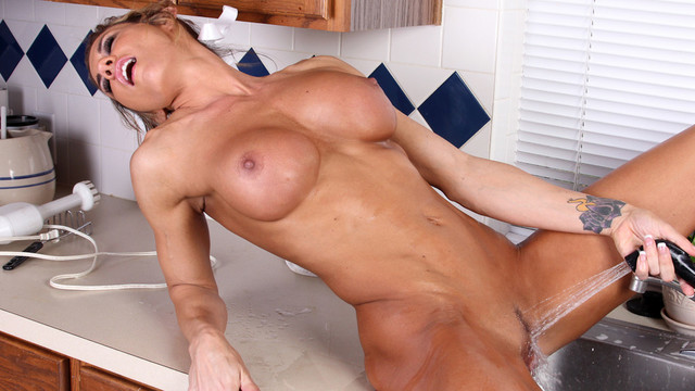 Sexy athletic mom uses the kitchen sink to