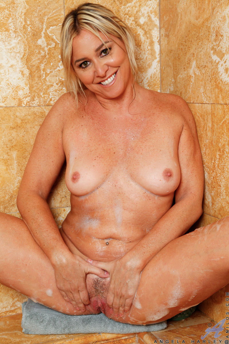 Angela Harley is a horny American milf who can't resist the urge to play with her all naturals and tanned skin in the shower. After soaping herself up beneath the spray, the cum craving cougar settles down on her shower's bench and spreads her legs to let