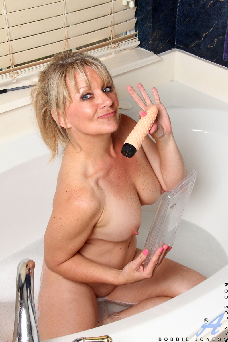 When 48 year old Bobbie Jones wants to indulge herself for the evening she always draws a warm bath and brings her waterproof sex toys for a good time! Covered in suds, this hot blonde babe runs slick hands over her big natural tits and down her curvy bod