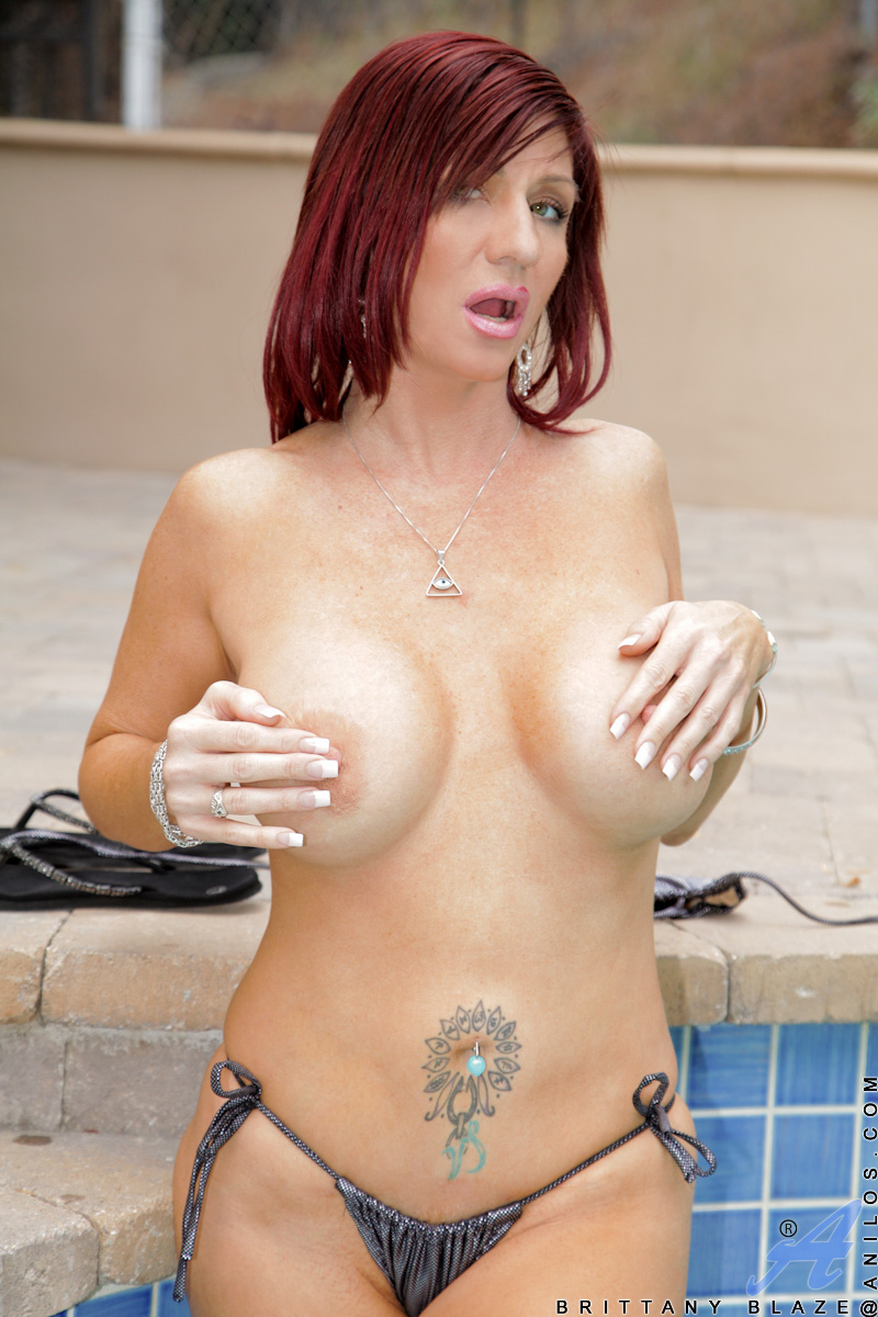Busty red haired Anilos flaunts her cleavage outside in a bikini