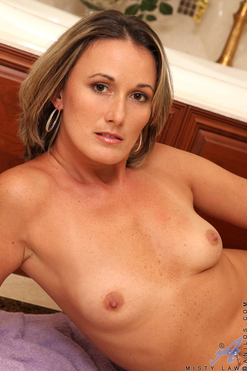 Leggy tan milf Misty Law plays with her wet pussy in the bathtub