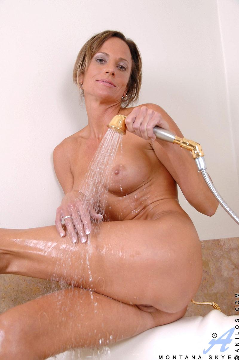 Tan well built milf with big tits masturbates in her bath tub