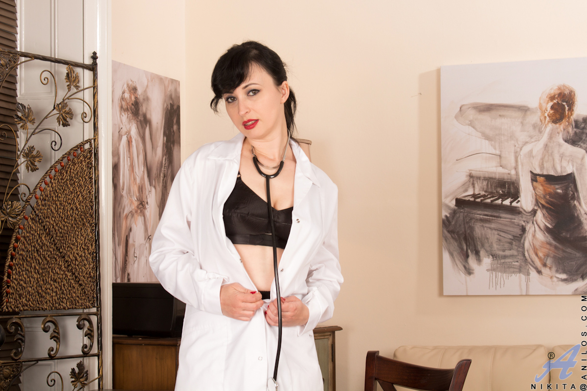 Raven haired hottie Nikita is a nurse who likes to play dress up. This naughty mom opens her lab coat to reveal her stunning body encased in black bra and garters. As her body warms up for fun, she slips out of her bra and then parts her thighs to show of