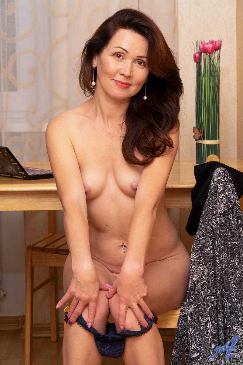 Pretty mommy Ptica is lovely as she starts stripping out of her work clothes. Her bra and pantyhose hit the floor, followed by her panties. Licking her fingers to get them wet, she fondles those fluffy titties and then shoves her fingers into her trimmed
