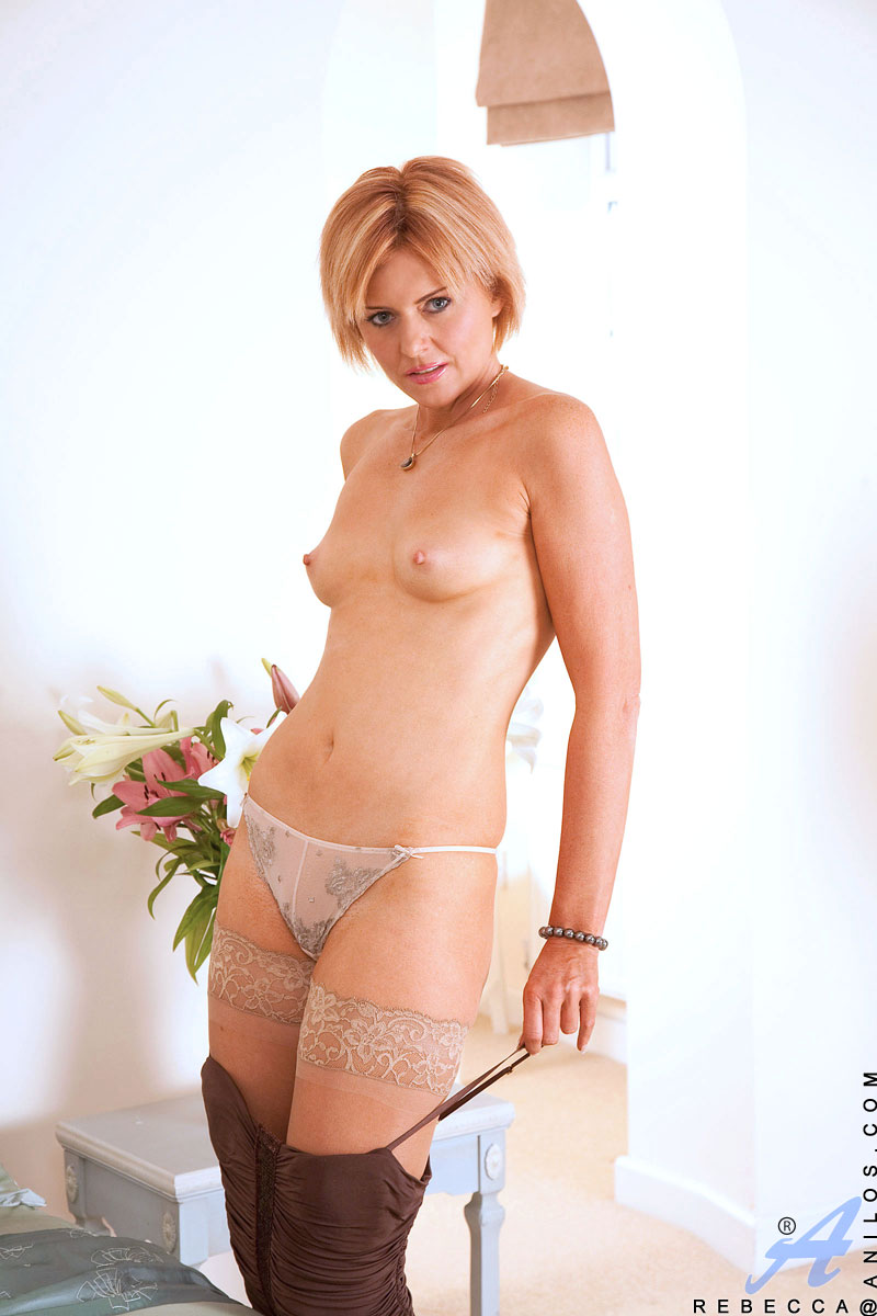 Foxy blonde cougar masturbates with a vibrator in her bed