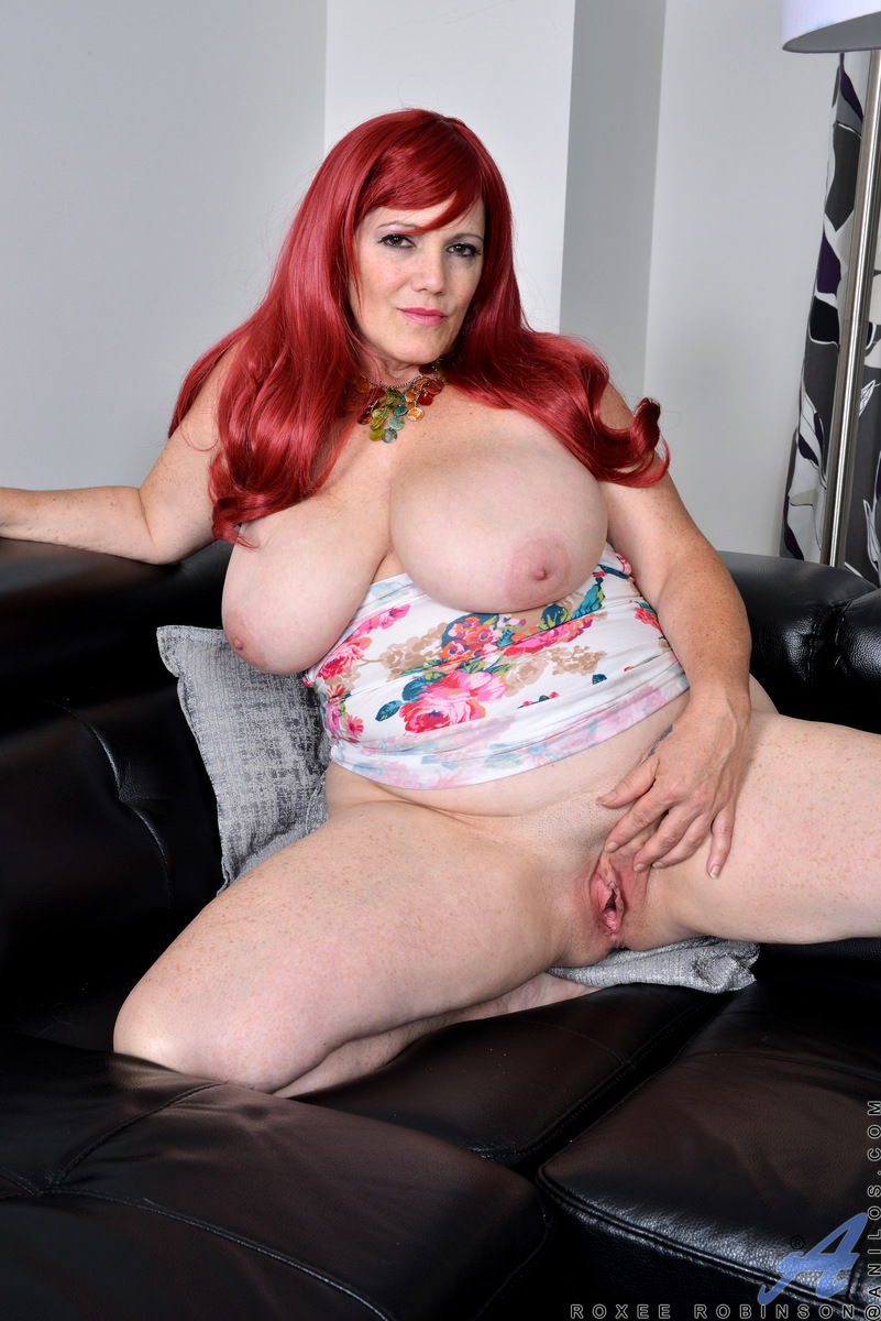Canadian redhead Roxee Robinson loves to wear tight dresses that show off all her lovely curves. Stripping down out of her bra and panties is second nature to this horny babe. She loves licking her own nipples, squeezing those giant jugs, and generally wo